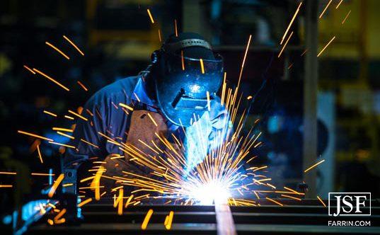 welder works on piece of metal while orange sparks fly