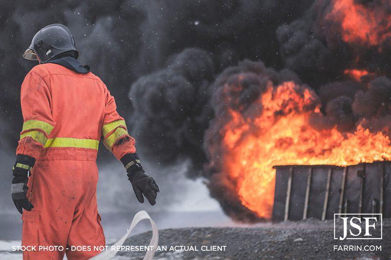A fireman in orange walking near a fire.