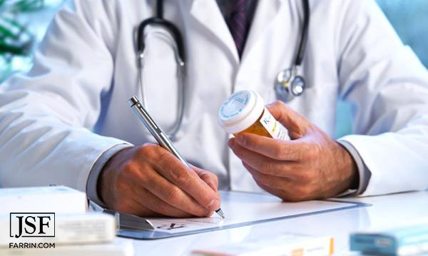 Doctor writing while holding a prescription bottle.
